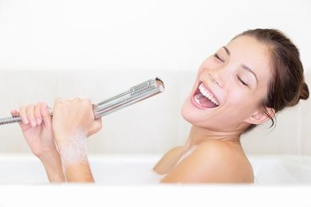 Kvinna i badkar sjunger med duschmunstycket som mic